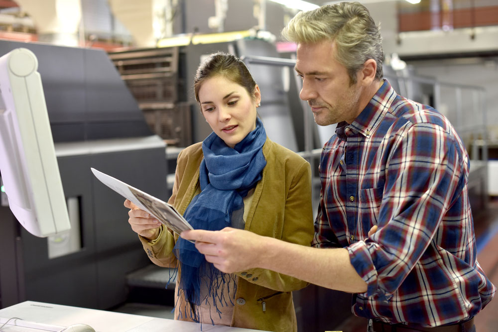 woman and man reviewiing print documents